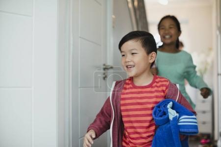 Foto de Niño y su hermana apuntan a la puerta de su casa para ir a nadar. El niño tiene una toalla enrollada en sus brazos - Imagen libre de derechos