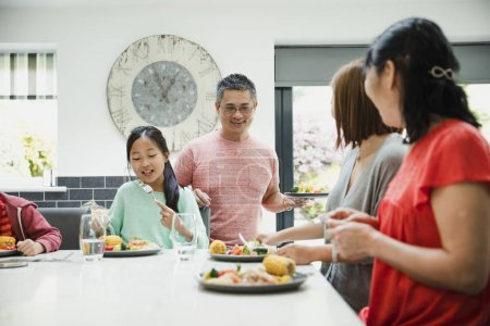 Photo for Family are sitting down to have their dinner together in the kitchen. They are eating a stir fry. - Royalty Free Image