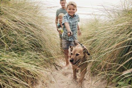 Photo pour Vue en angle bas d'un petit garçon et sa famille promenant le chien à travers les dunes de sable . - image libre de droit