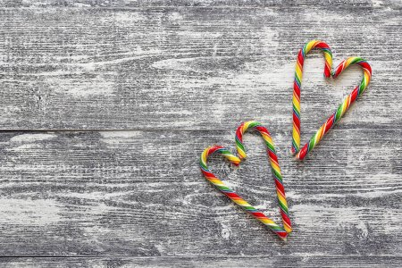Christmas Candy Canes in the form of heart on gray wooden table.