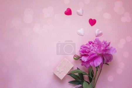 Romantic background with peony, gift box and hearts on pink.