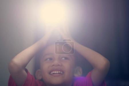 A boy holding a camera flash on his head
