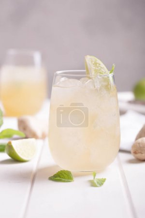 Photo for Fresh cocktail prepared with ginger beer, lime and ice. Beverage on the table - Royalty Free Image