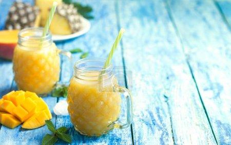 Photo pour Smoothie à l'ananas frais et à la mangue dans deux verres avec des fruits sur un fond rustique en bois torqué. Boissons d'été fraîchement mélangées, agréables à énergiser pendant une journée chaude . - image libre de droit