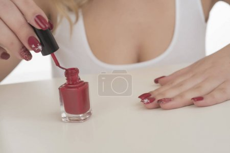 Manicure process at home. Woman painting her nails on white background