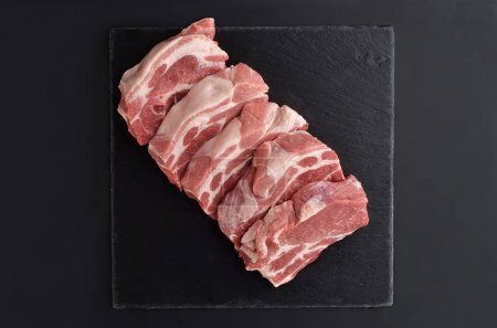 Photo for Five fresh raw boneless pork shoulder butt slices on black stone plate. Top view. - Royalty Free Image