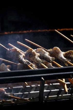 skewer fish on barbecue black background grill