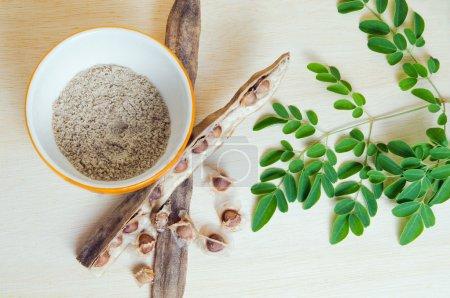 Moringa leaf and Moringa seed on wooden board background