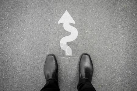 Businessman standing on the street and hard and difficult way ahead direction floor sign in front of him