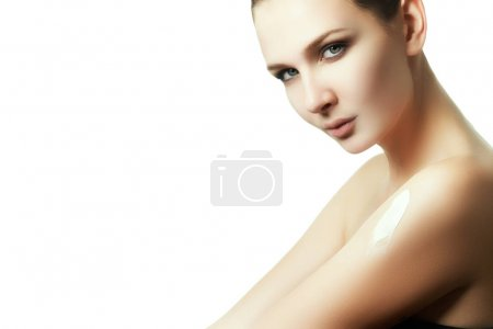 Photo for Creaming body after bathing. The woman rubbed into the skin lotion. Beauty face portrait. Beautiful spa model girl with perfect fresh clean skin. Brunette female smiling. Youth and skin care concept - Royalty Free Image