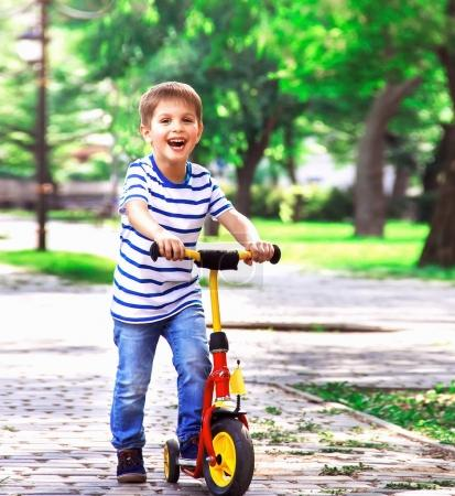 cheerful boy on a scooter, playing in the park on a background o