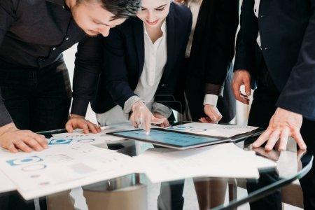 Photo pour Réunion de bureau. équipe d'affaires remue-méninges. groupe de travailleurs étudient des documents sur ordinateur portable avec des graphiques et des diagrammes. analyse de l'information - image libre de droit