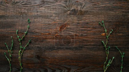 Photo for Brown rustic wooden background. Green thyme sprig decor. - Royalty Free Image