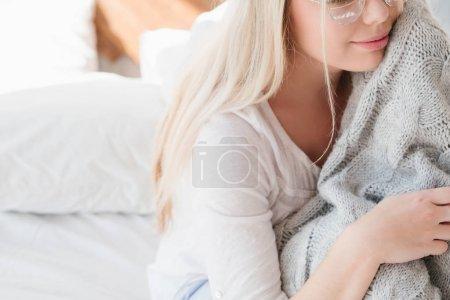 Photo pour Matin d'hiver confortable. Dame paisible et détendue avec couverture tricotée chaude grise dans la chambre . - image libre de droit