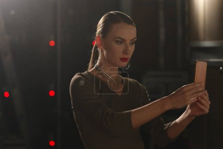 Pretty fashion model in makeup making selfe with smartphone camera on backstage