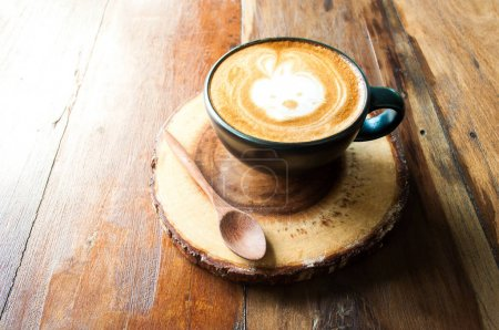 Cute Hot Cappuccino Coffee on wooden saucer with soft sunlight