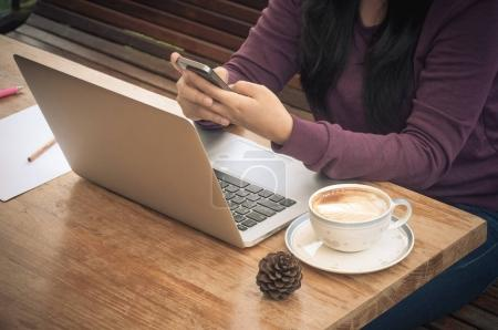 Vintage tone image for woman hold mobile phone in her hands on working time