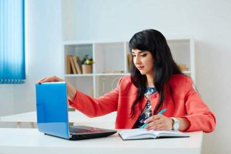 Attractive business woman working at laptop in office