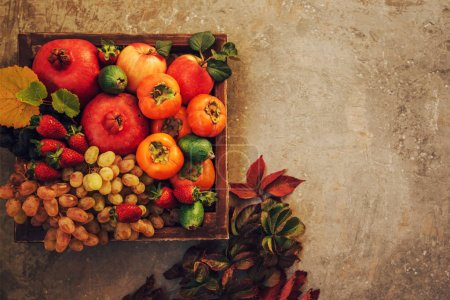 Photo for Apples, pomegranate, grapes with autumn yellow leaves on a vintage tray. Healthy food clean eating selection. Fruits on gray concrete background. Flat lay with copy space. - Royalty Free Image