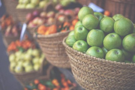 Photo for Market stall with variety of organic vegetable. Fresh organic produce on sale at the local farmers market. Ripe organic apples in a basket. - Royalty Free Image