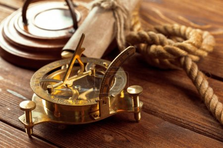 Compass and rope on wooden table, close up.