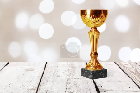 golden trophy on wooden table