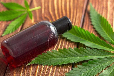 Cannabis leaves and oil on wooden background