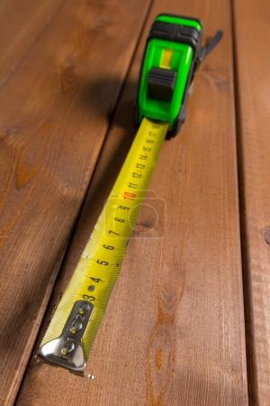 Tape measure on wooden background, top view.