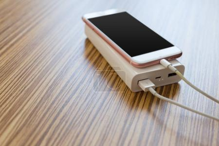 powerbank and cellphone on wooden table, modern gadgets background