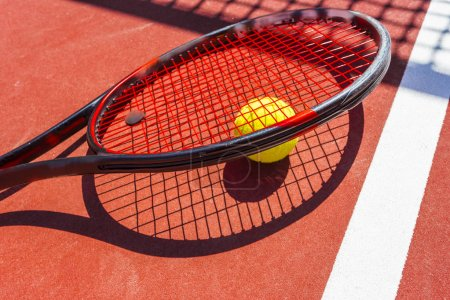 Tennis ball and racket on the grass court