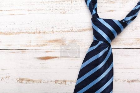 Fashionable male tie over wooden background