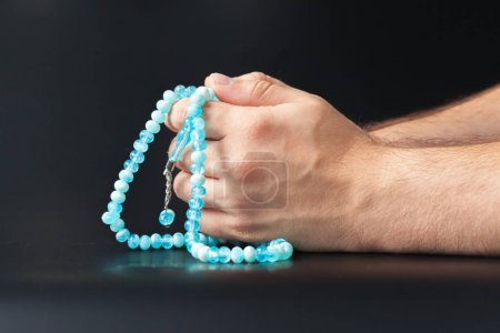 Male hands holding beads