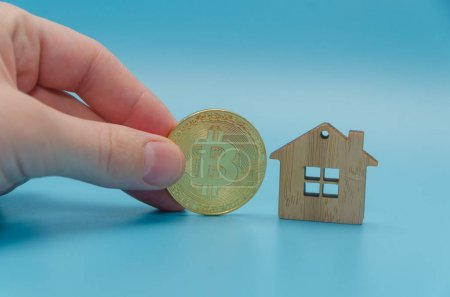 wooden house, toy and Golden bitcoin cryptocurrency, on blue bac