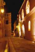 Illuminated streets of Mdina, ancient capital of Malta. Night view on buildings and wall decorations of ancient town.