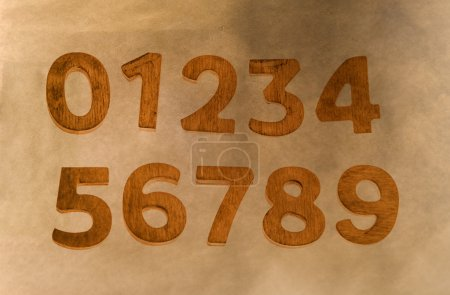 Photo for Wooden storage numbers isolated on brown paper background - Royalty Free Image