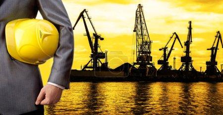 Photo pour Pas de visage. Personne méconnaissable. torse de l'ingénieur tenant dans la main casque jaune pour la sécurité des travailleurs sur les grues dans le fond du port . - image libre de droit