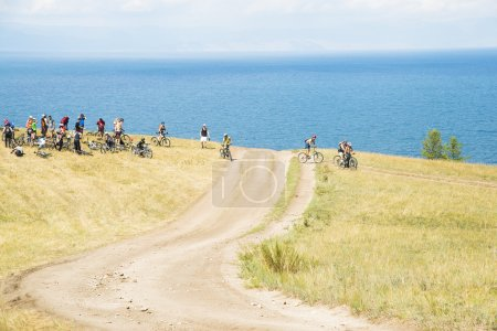 Bicyclists on hill above Baikal lake