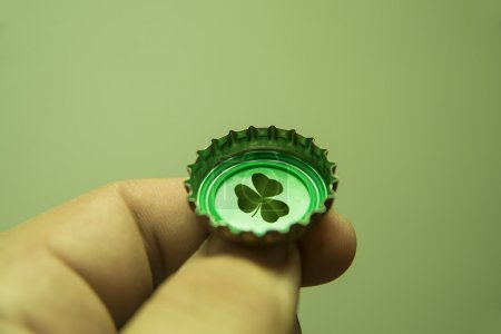 fingers hold Bottle Cap with leaf