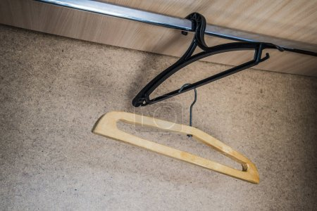 Photo for Wooden and plastic hangers  hanging in an empty closet - Royalty Free Image