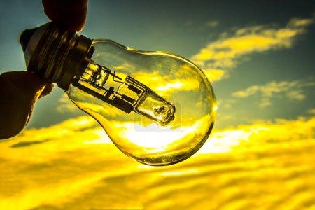 Photo pour Ampoule au-dessus de fond de coucher de soleil. ampoule lampe transparente dans la main de l'homme. alternative erergy solaire dans la ville, vie de nuit de la ville. Simbol, concept de nouvelle idée créatrice d'entreprise. Économiser de l'énergie eco. - image libre de droit