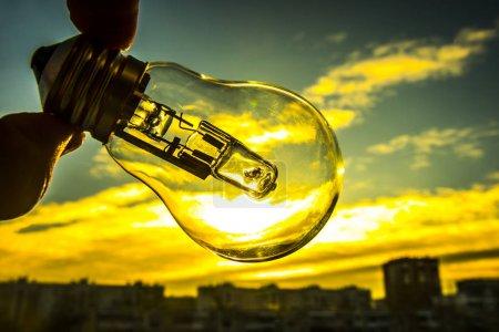 Photo pour Ampoule au-dessus de Sunset urbain abrite. ampoule de lampe dans la main de l'homme sur le toit de maison sur fond transparent. alternative erergy solaire dans urbain, ville, vie de nuit de la ville. Simbol, concept de nouvelle idée créatrice d'entreprise. Économiser de l'énergie eco. - image libre de droit