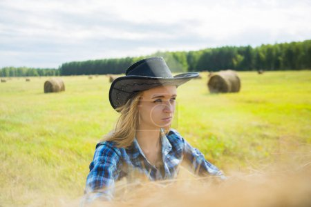 Cowgirl standing  near haystack