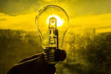 Photo pour Ampoule au-dessus de fond de coucher de soleil. lampe en main de l'homme. alternative erergy solaire dans la ville, idée créative. Économiser de l'énergie eco. - image libre de droit