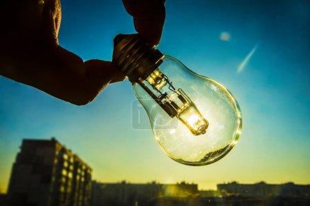 Photo pour Ampoule électrique à la main sur fond de ciel bleu. idée d'énergie solaire alternative. - image libre de droit