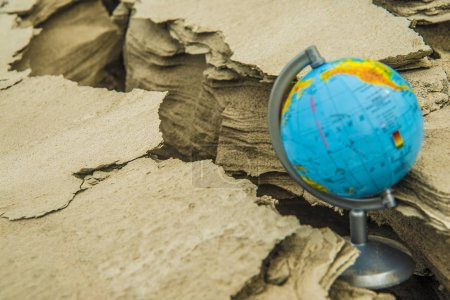 Photo for Globe  stands in cracked soil.   dry desert - Royalty Free Image