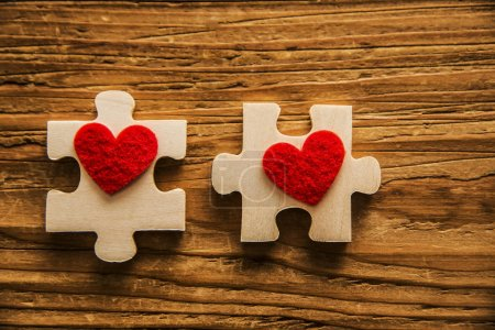 2 puzzles.Two red hearts on wooden parts on table ...