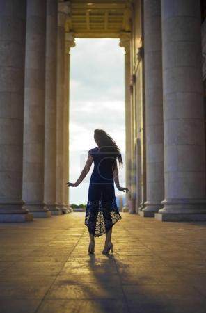 girl dancing between columns.