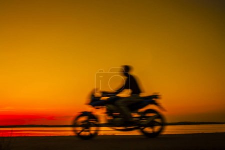 blurred motorcyclist against sky