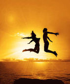 family  on the beach.  Silhouette of a couple - man and woman jumping on the beach on sunset background