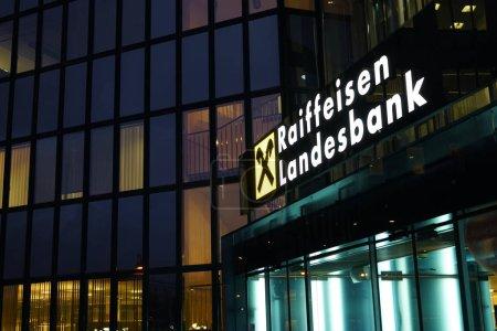 LINZ, AUSTRIA - NOVEMBER 13, 2017:  Illuminated sign of Raiffeisen Bank on wall of modern business center building. night scene